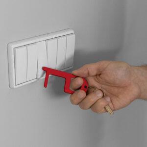 Gancho higiénico metálico rojo dando a un botón
